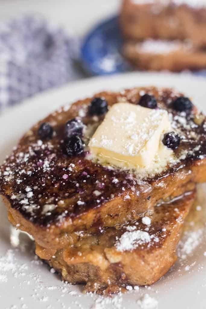 close up shot of two slices of sourdough French toast with butter and blue berries on a white plate