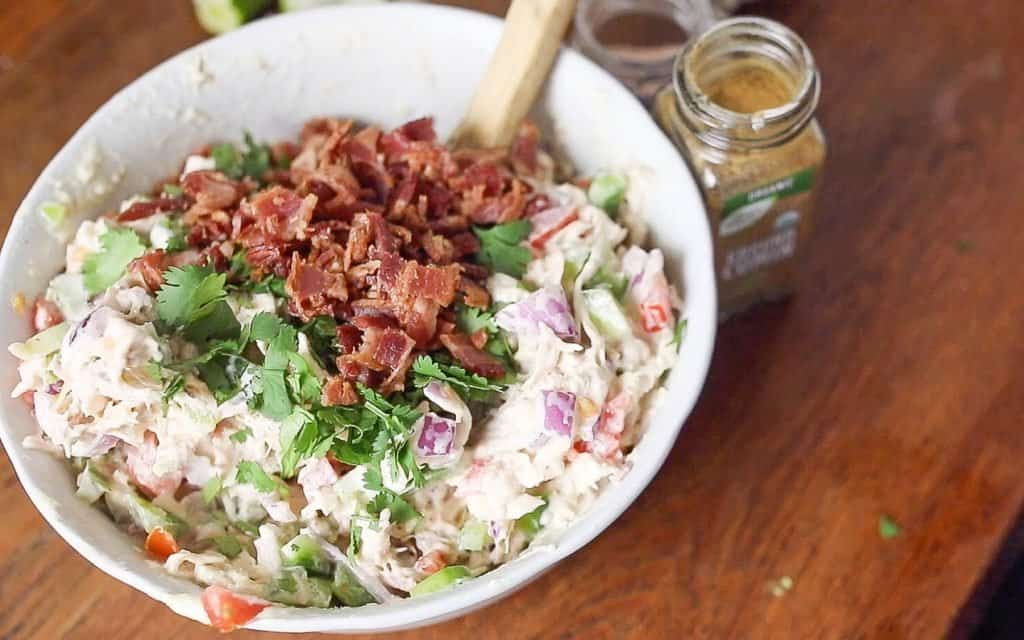 bacon and cilantro added to a bowl of chicken salad