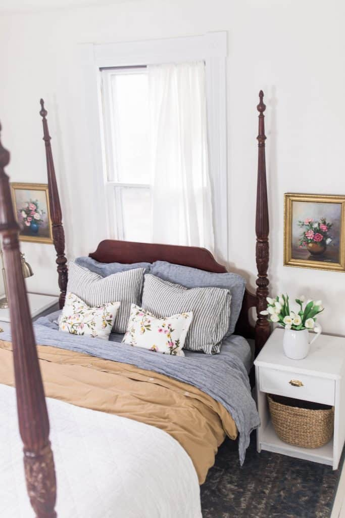 Victorian four poster bed with white, gold and blue stripped linens. Linen pillows are stacked against the headboard. To the right of the bed is a white nightstand with vase of flowers on top and gold framed art