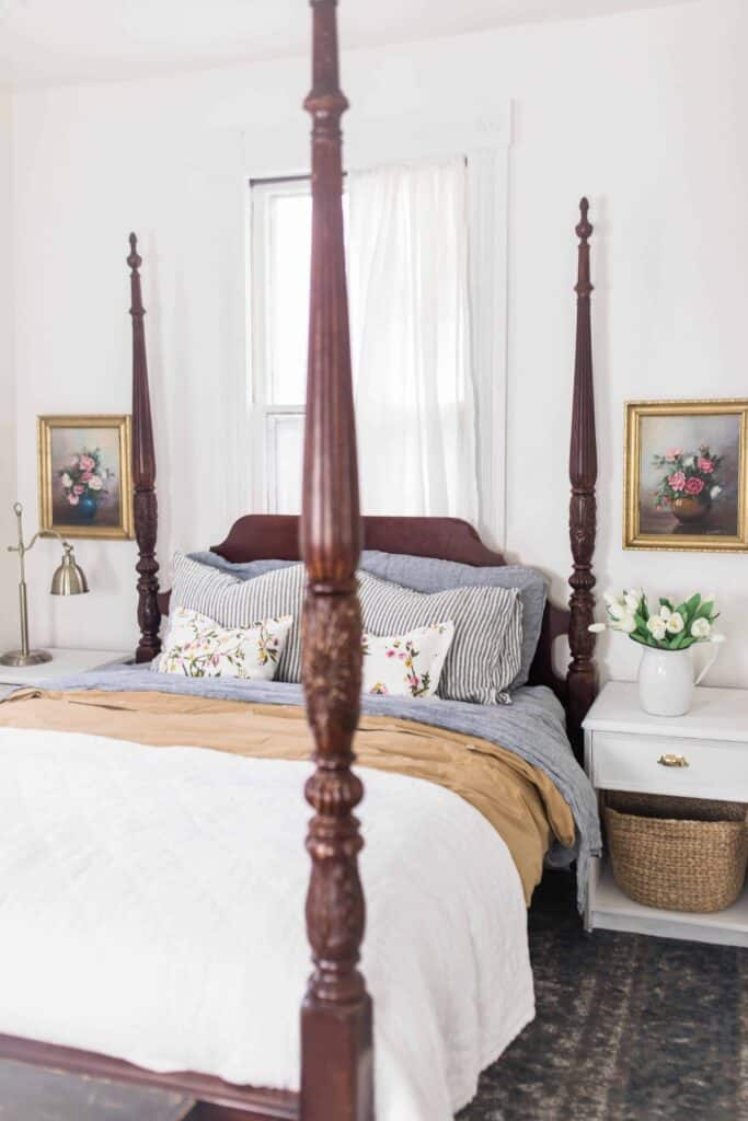 Beautiful dark wood four poster bed draped with linen bedding. White nightstands with a bottom basket to the right. Antique floral pictures with gold frames hang over the nightstands