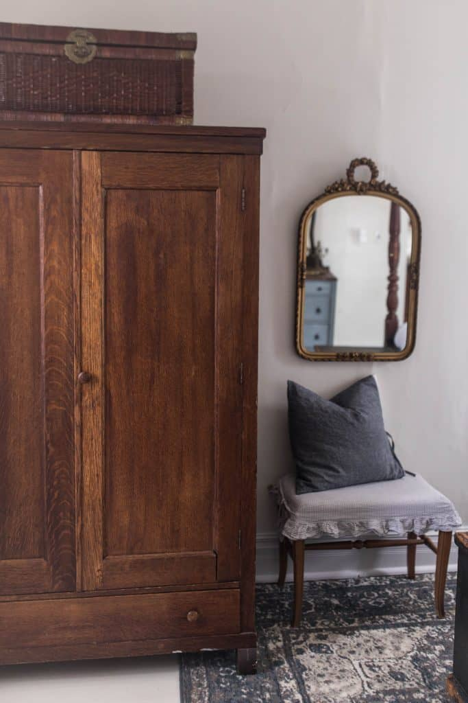 Large wood armoire with a woven chest on top. A footstool with ruffle slipcover and pillow to the right. A mirror hanging over the bench
