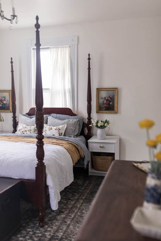 side view of a four poster bed with white, gold, and blue linens. Linen striped and floral pillows stacked on the bed. The top of a dresser with yellow florals in a vase to the side