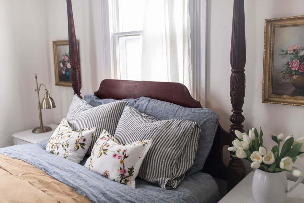 close up of beautiful linen and floral pillows on a wooden headboard.