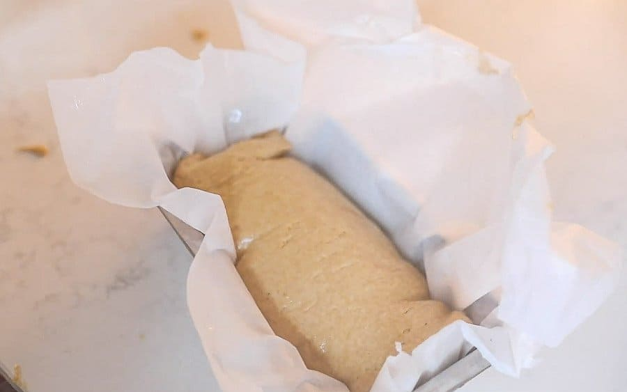 einkorn bread dough in a parchment lined bread loaf pan