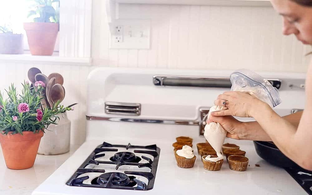 women pipping lemon whipped cream over muffins