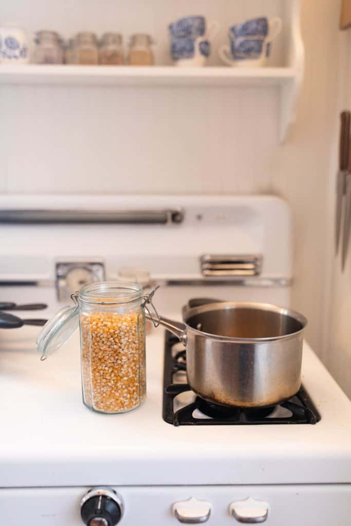stainless steel pot on the stove with a jar of popcorn kernels to the left