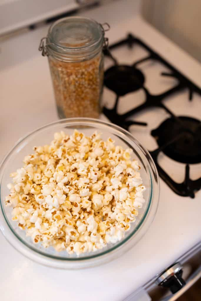 popcorn in a glass bowl on top a stove-top
