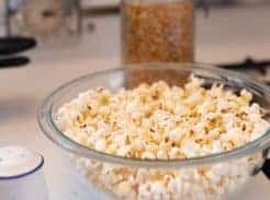 homemade coconut oil popcorn in a glass bowl on a stove top. popcorn kernels in the behind the bowl