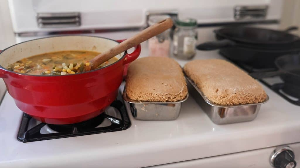 two loaves of einkorn bread in loaf pans next to a pot of soup on the oven