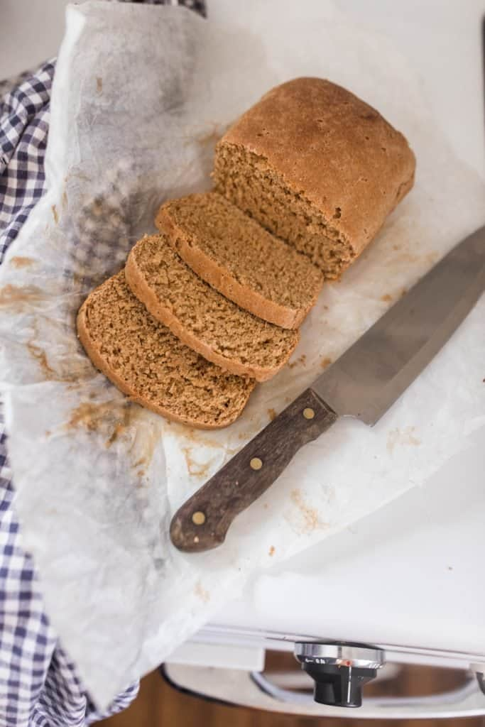overhead shot of sliced einkorn sandwich break on parchment paper. A knife lays to the right and a checked towel to the left