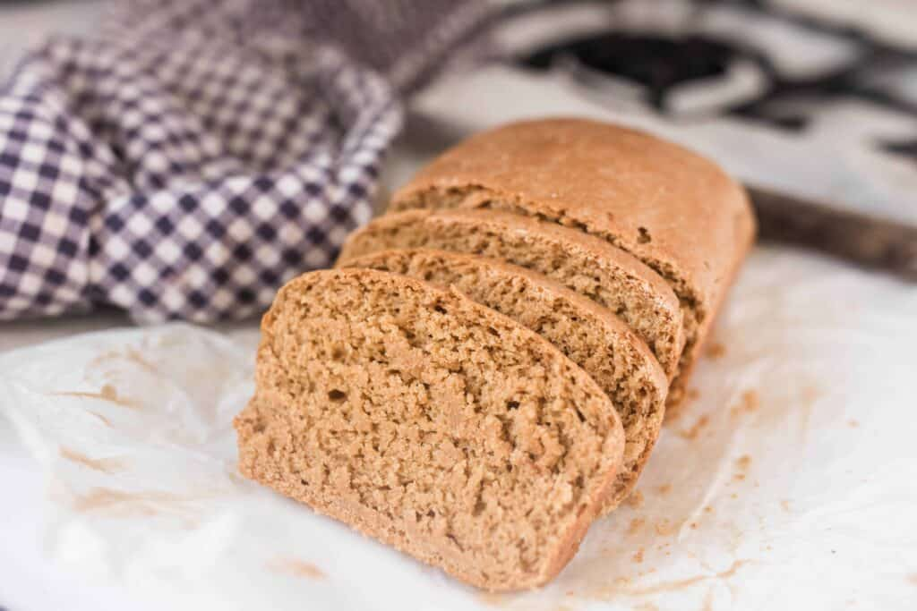 einkorn sandwich bread sliced on a stove top with a blue and white checked towel in the background