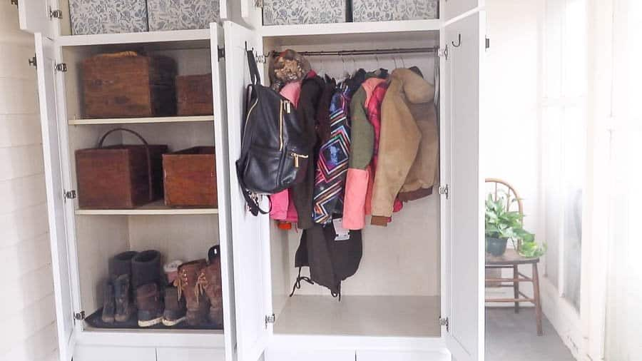 farmhouse mud room organization with coats hanging on one side and bins on the other