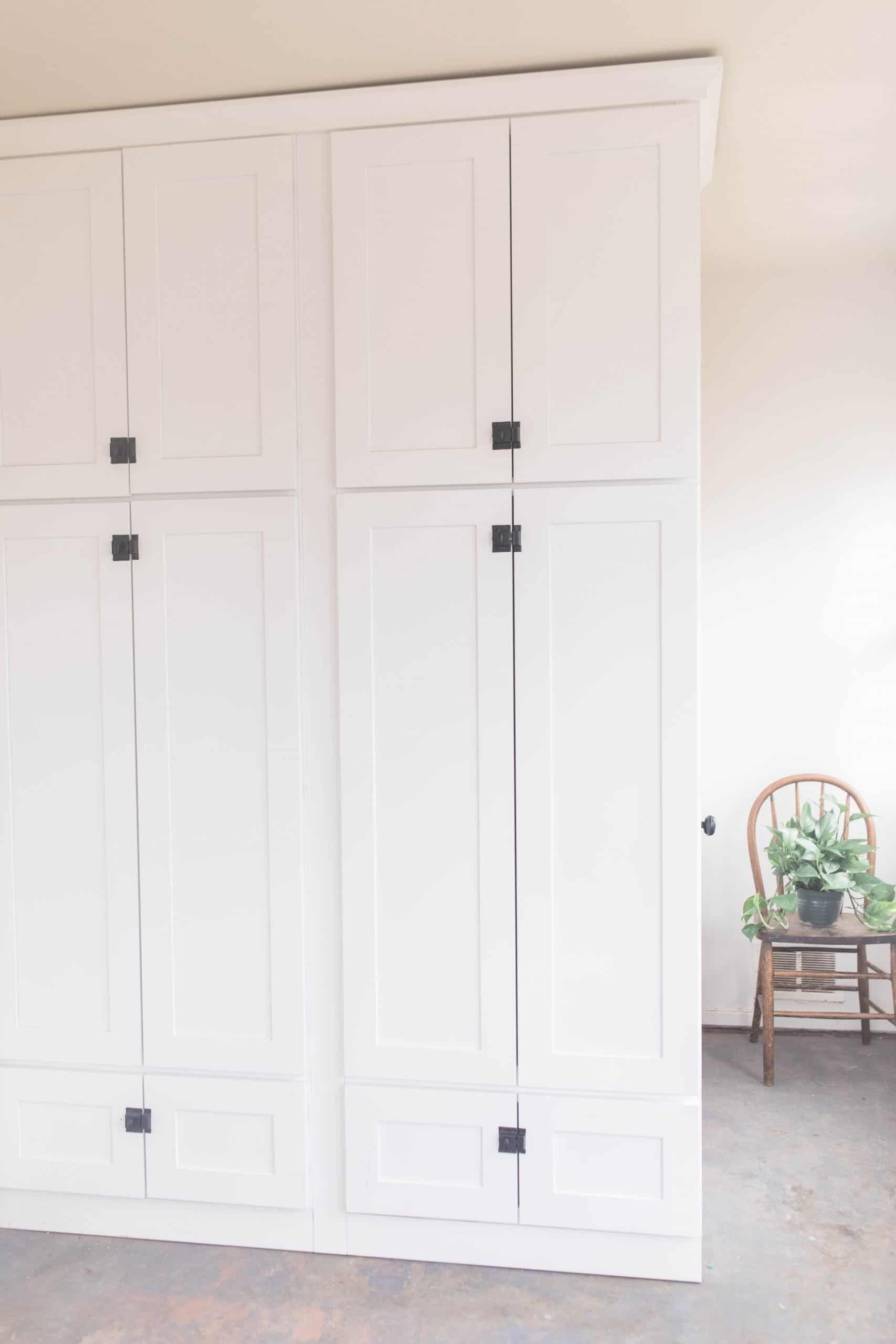 farmhouse mudroom with large white cabinets with black latches, gray painted floors, and a chair with a plant in the background