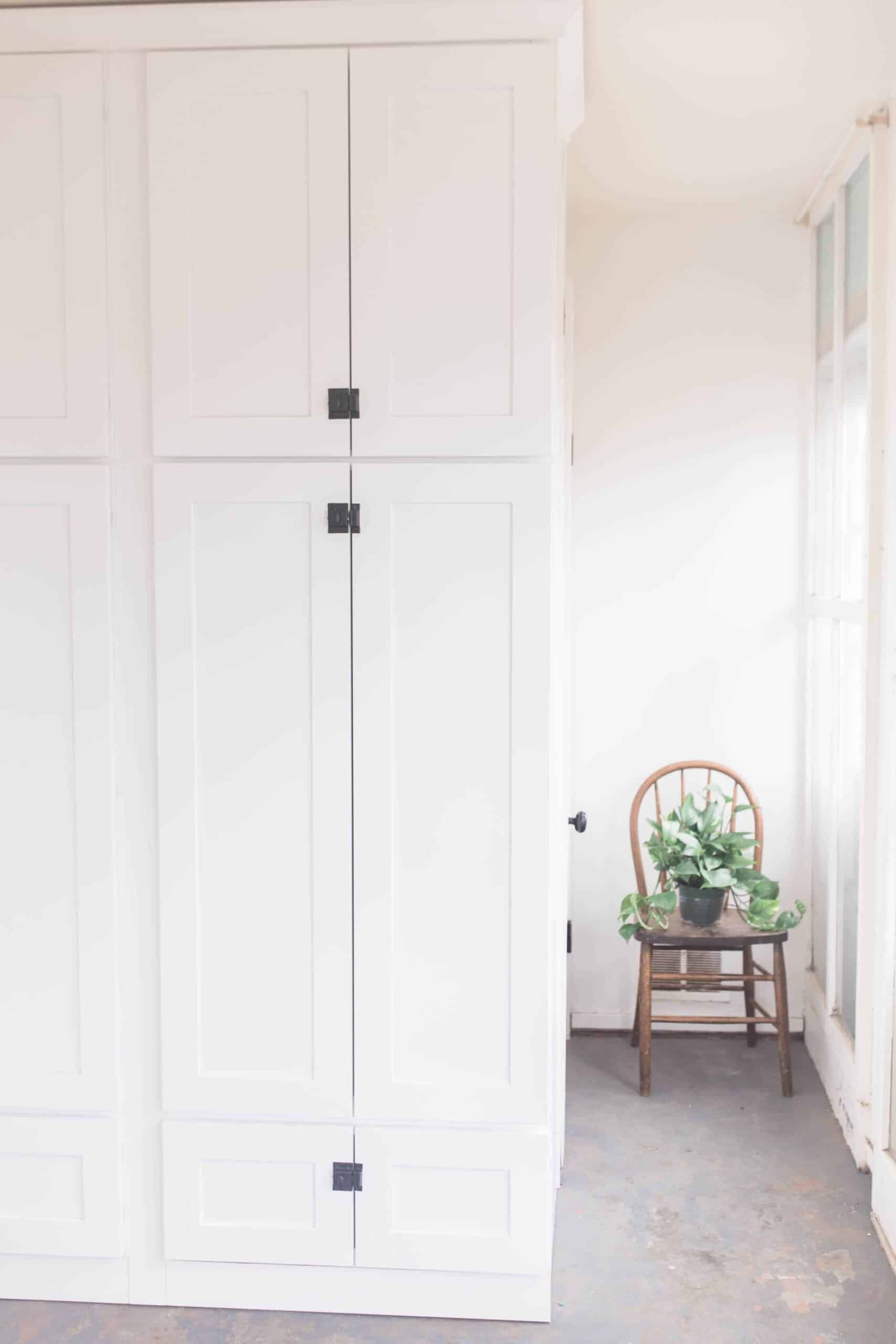 large white cabinets with black latches for farmhouse mud room organization