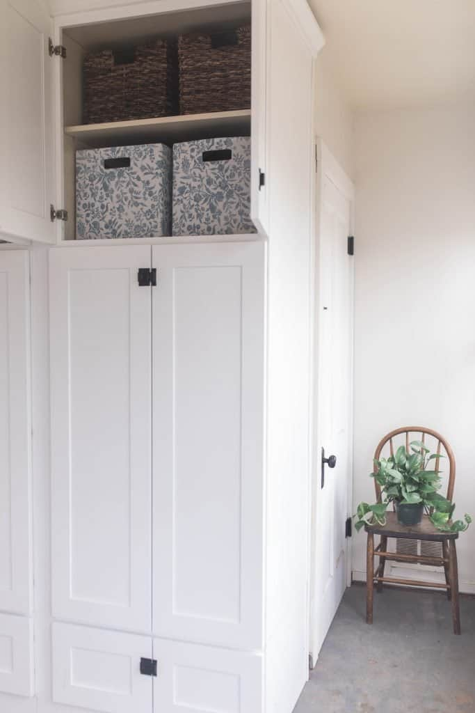 large white cabinet with bin organization. A chair with a plant to the right