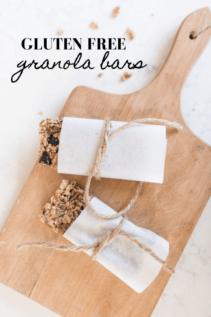 two homemade granola bars wrapped in parchment paper and tied with twine on a wood cutting bar
