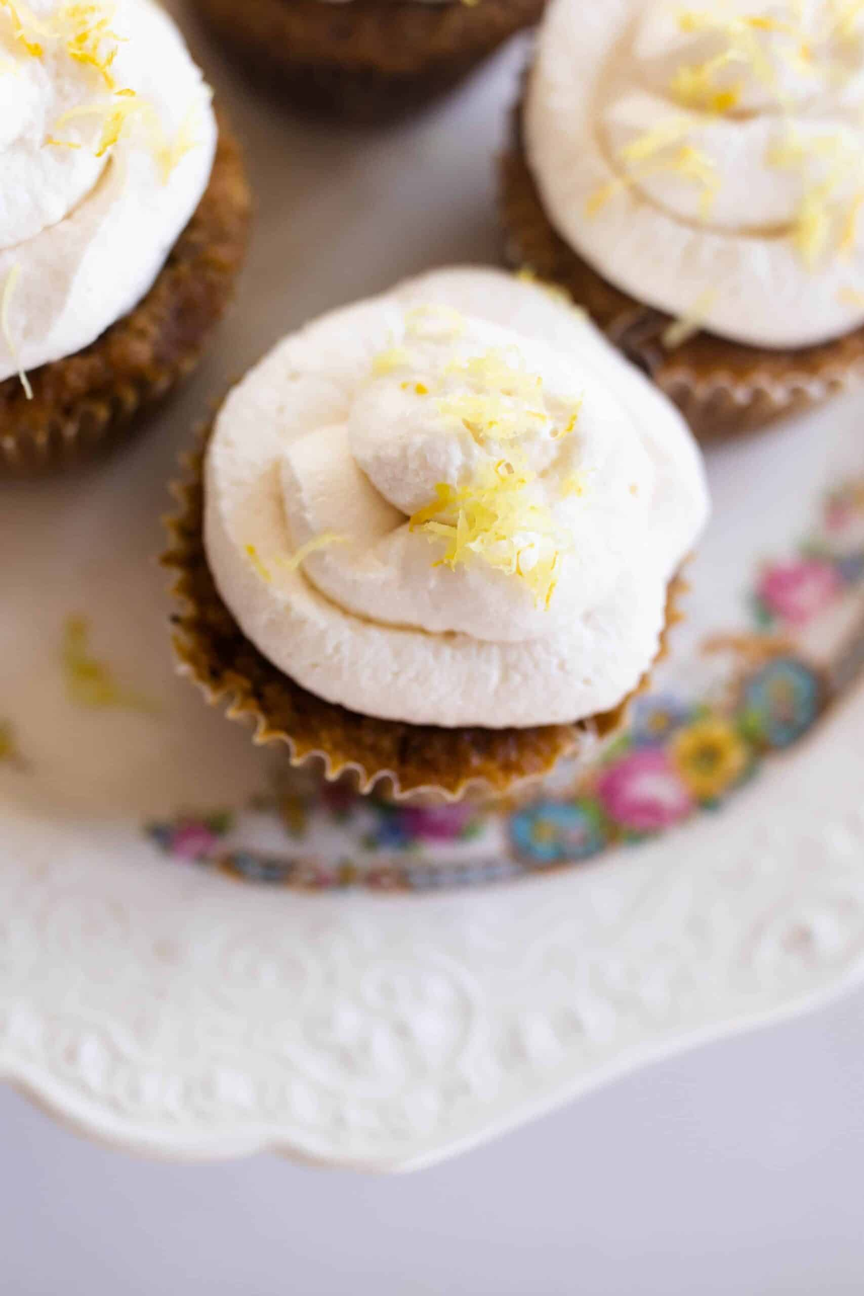 overhead shot of muffins with lemon whipped cream frosting topped with lemon zest.