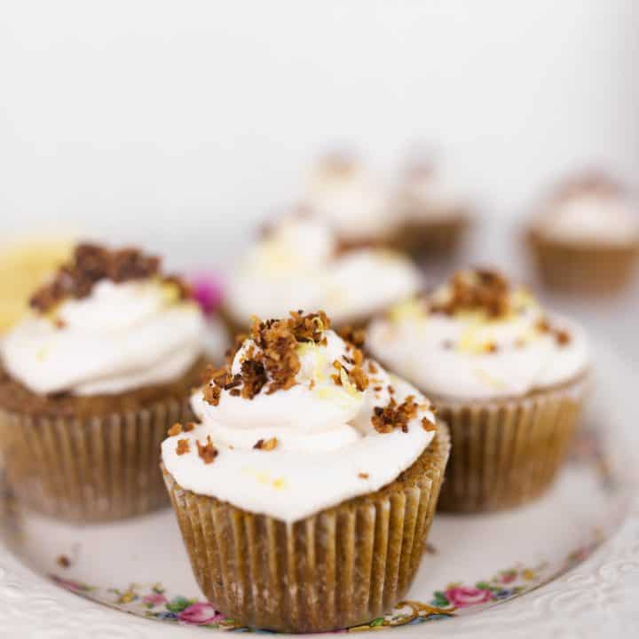 coconut flour lemon poppy seed muffins topped with whipped cream, toasted coconut and pink flowers