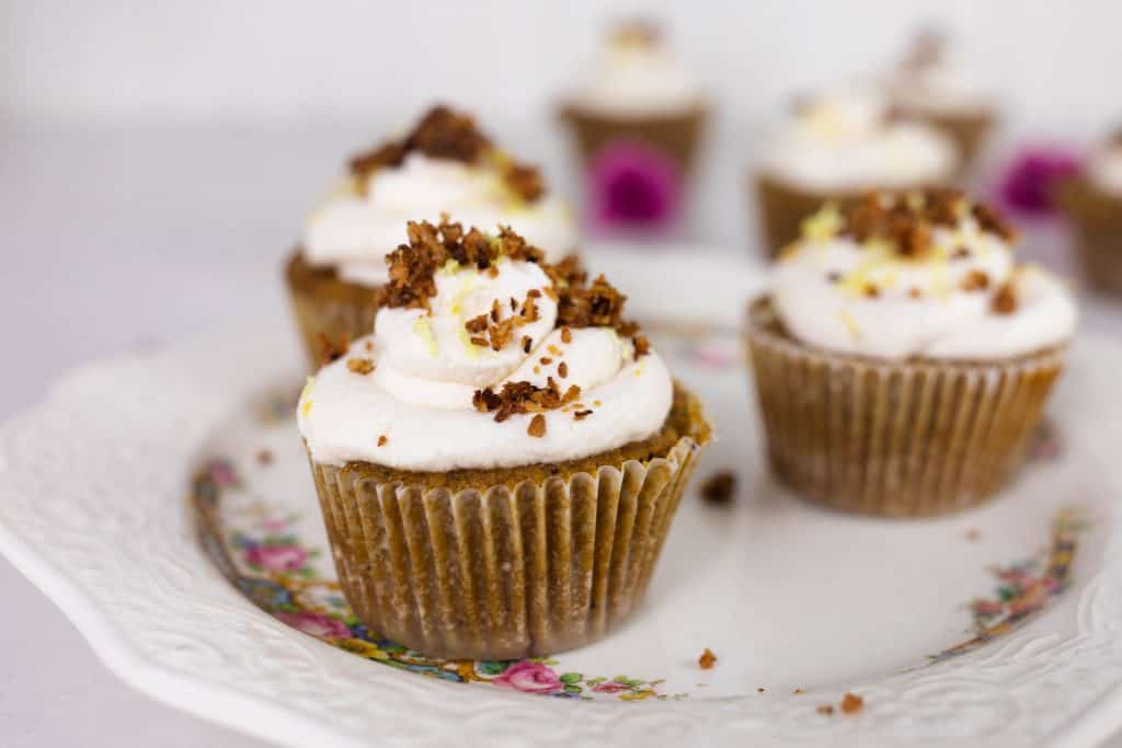 three muffins topped with frosting, lemon zest and toasted coconut on a antique plate