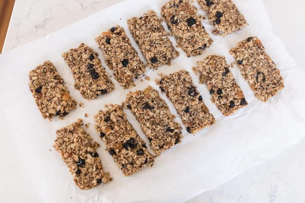 granola cut into 12 even bars on parchment paper.