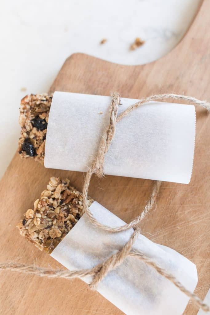 rustic granola bars wrapped in parchment paper and tied with twine on a cutting board