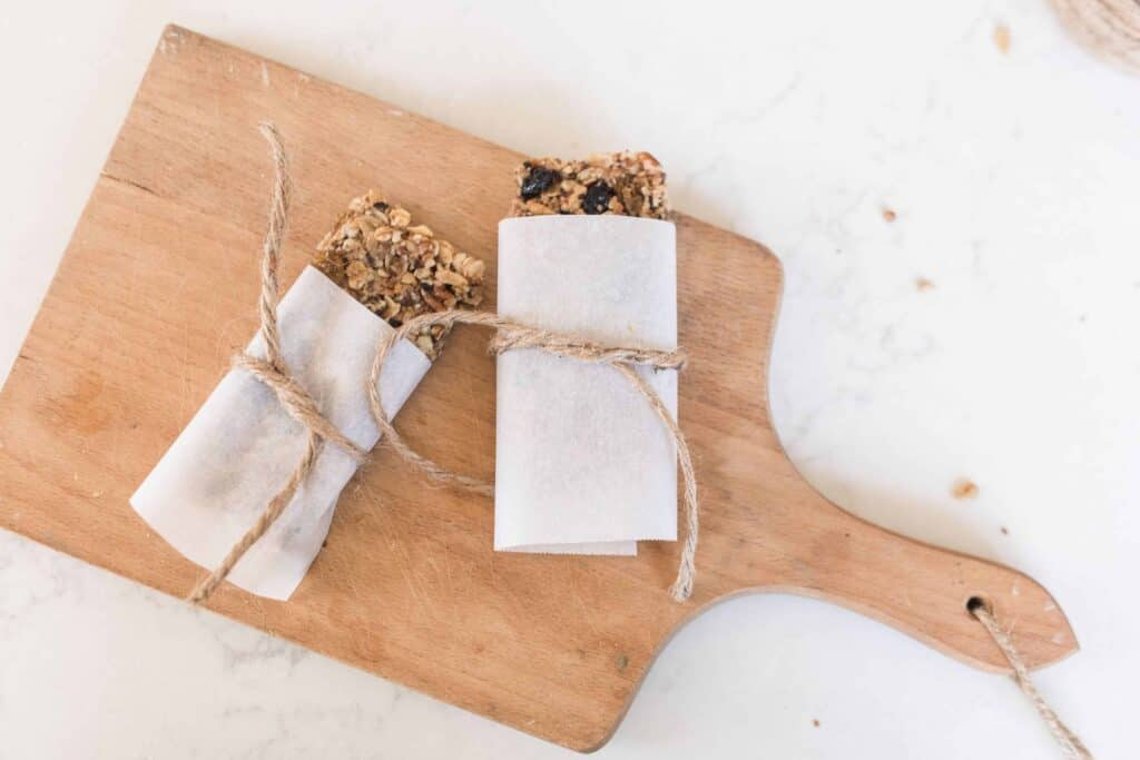 two gluten free granola bars wrapped with parchment paper and tied with twine on a wood cutting board on a quarts countertop
