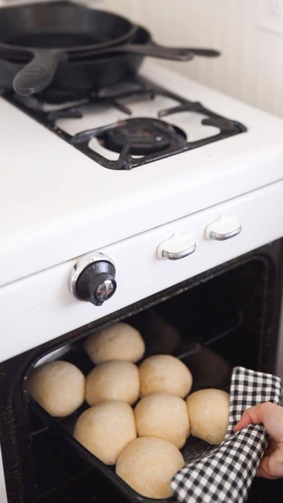 women hand taking our sourdough rolls out of an antique stove with a blue and white towel