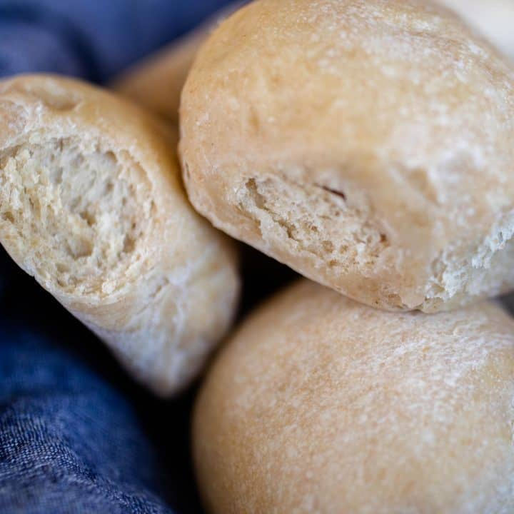 sourdough diner rolls stacked in a blue towel lining a basket