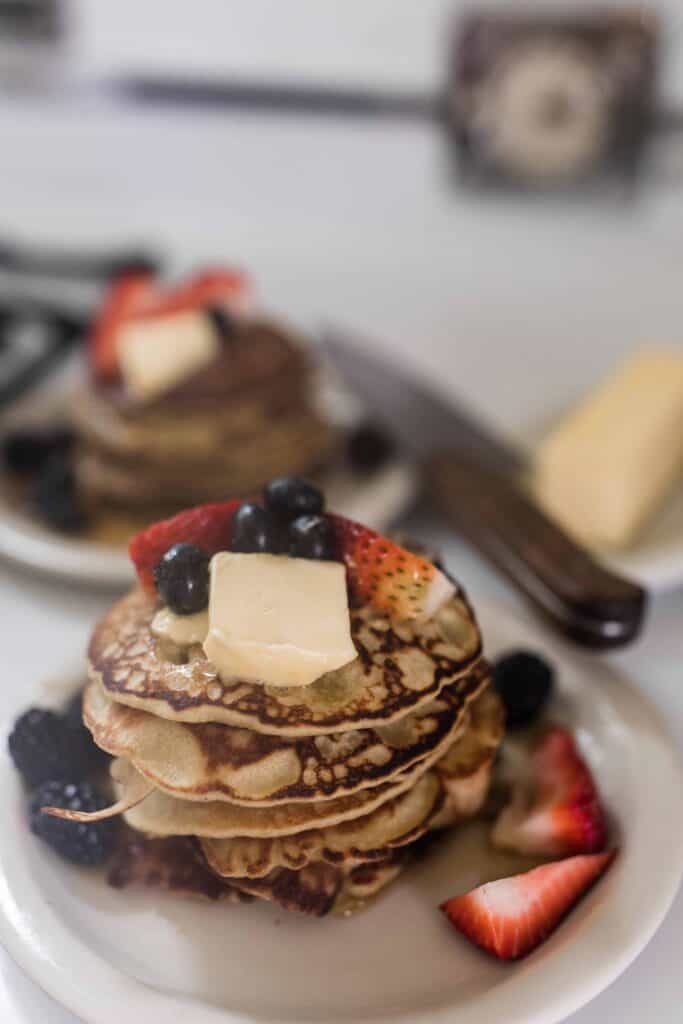 two stacks of buckwheat pancakes topped with fresh fruit and butter on white places