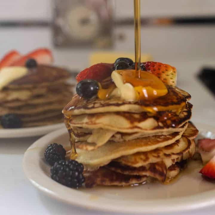 maple syrup being poured over a stack of buckwheat pancakes topped with butter and fruit