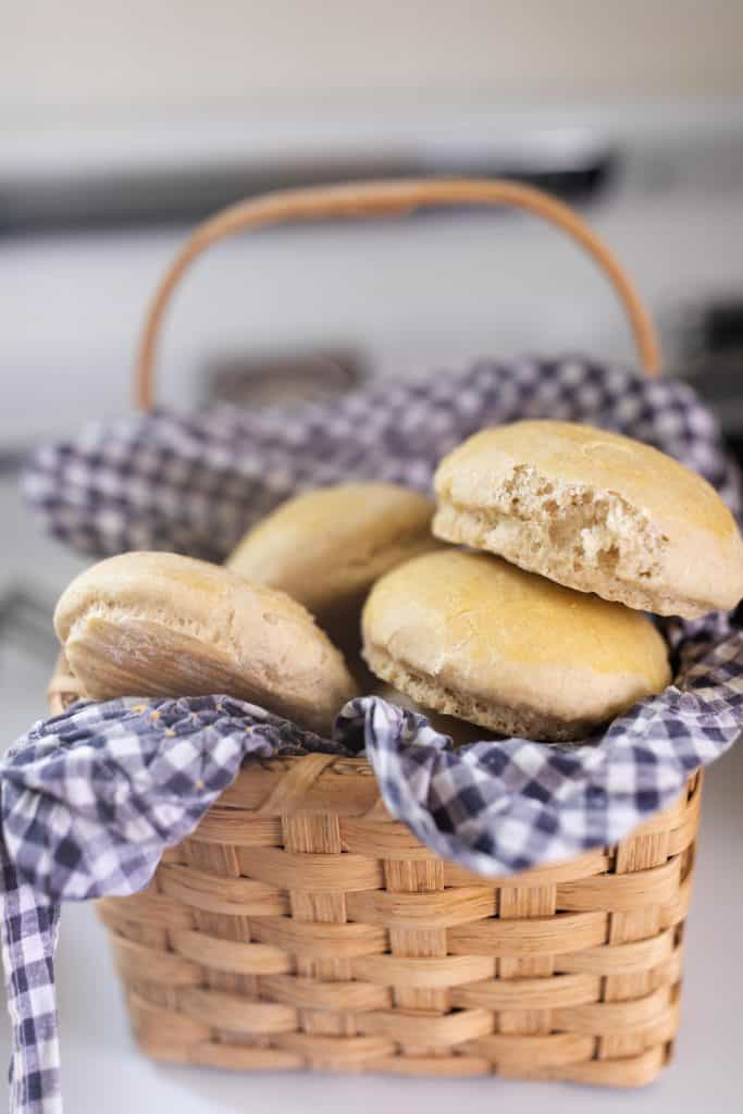a basket lined with a blue and white check with four sourdough buns