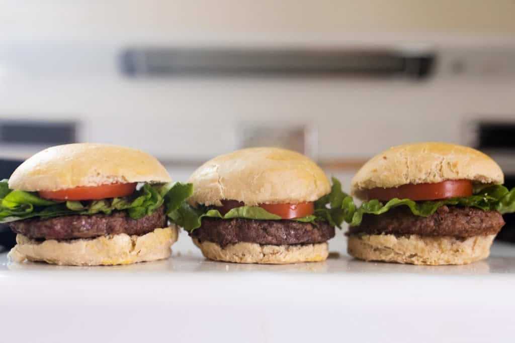 three hamburgers with tomatoes on lettuce on homemade sourdough buns