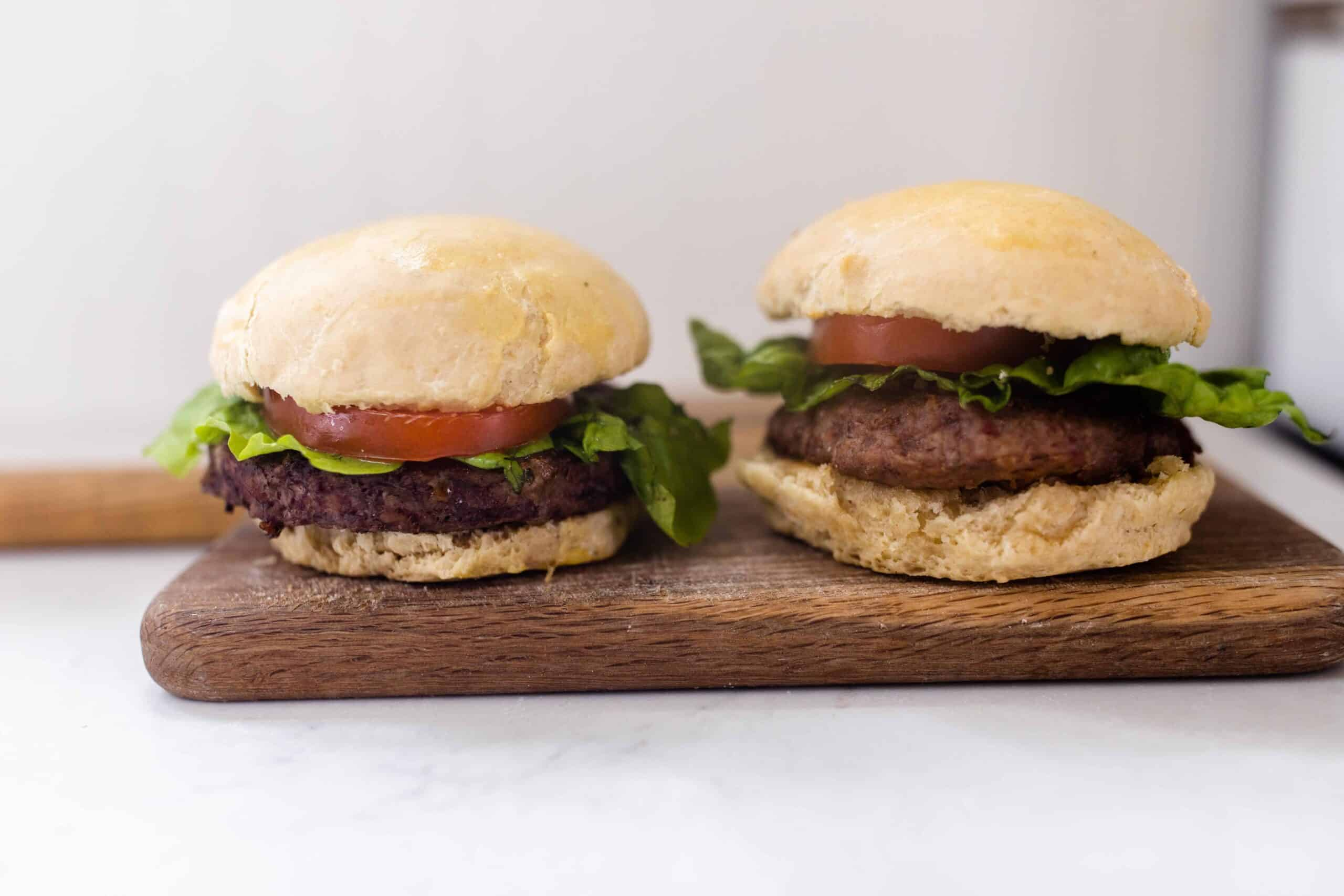 two burgers with tomato and lettuce on homemade sourdough buns on a cutting board