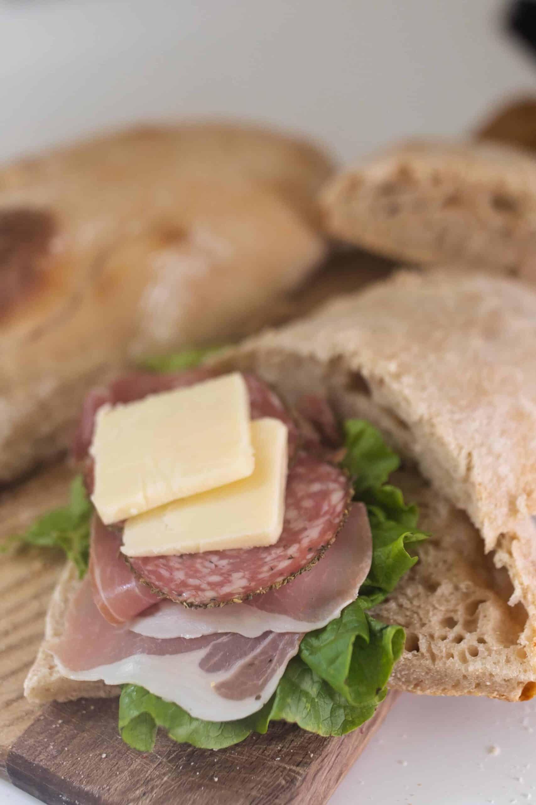 prosciutto, salami, lettuce, and cheese on sourdough ciabatta bread