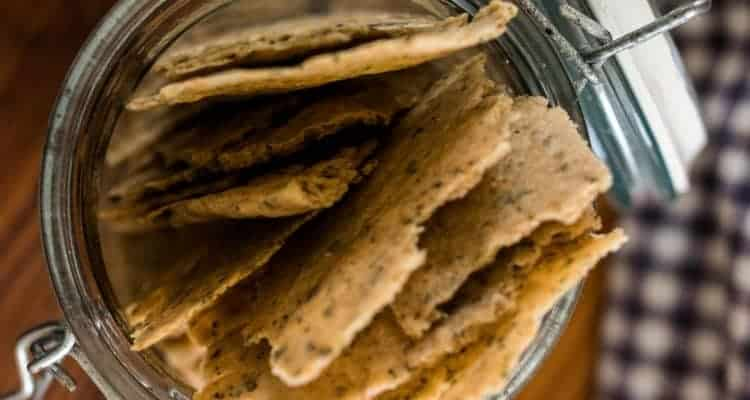 overhead shot of homemade sourdough crackers in a glass jar with lid. A white and blue checked towel is to the right