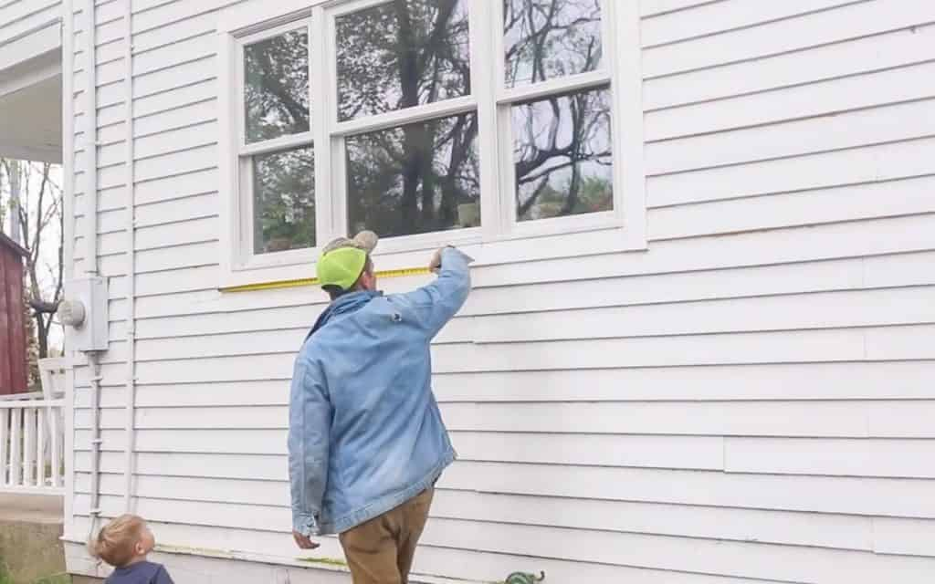 man measuring a window including the trim to make a diy window box
