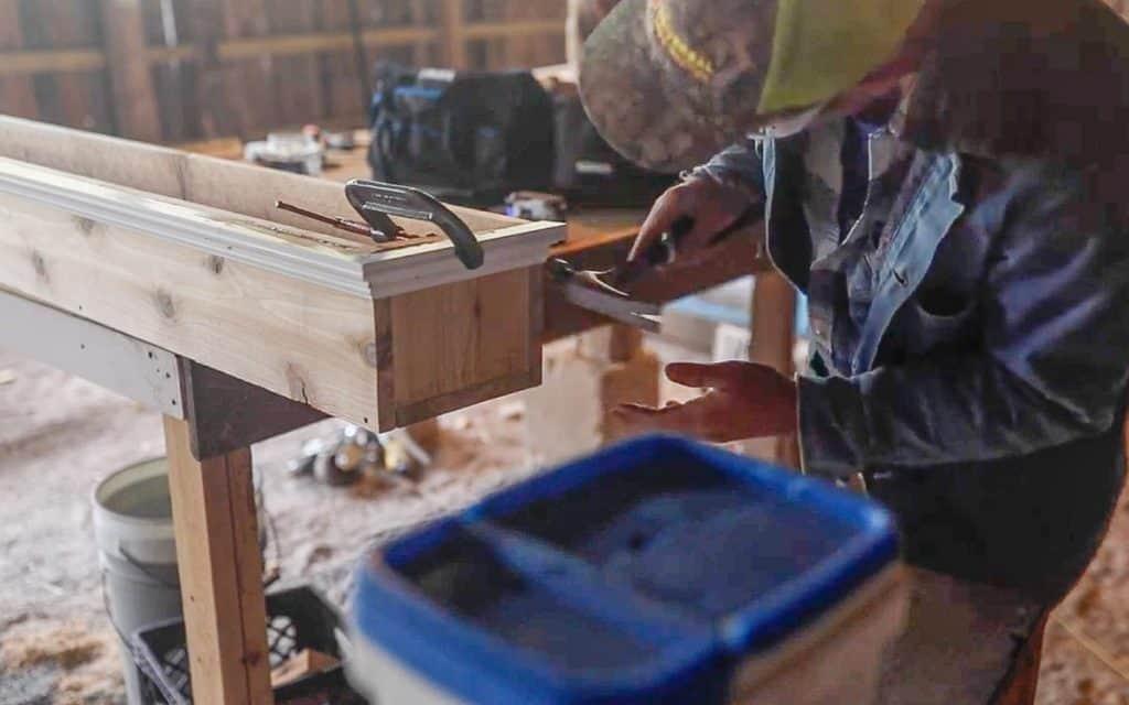 man hammering decorative trim on a diy window box using finishing nails