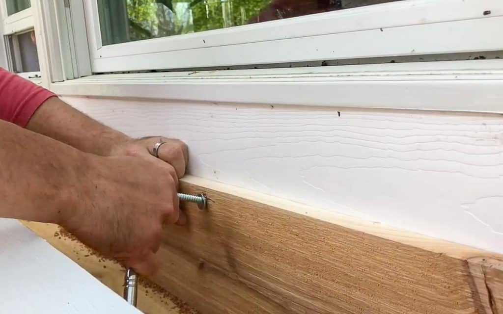 hanging a DIY window box using lag bolds and a wrench