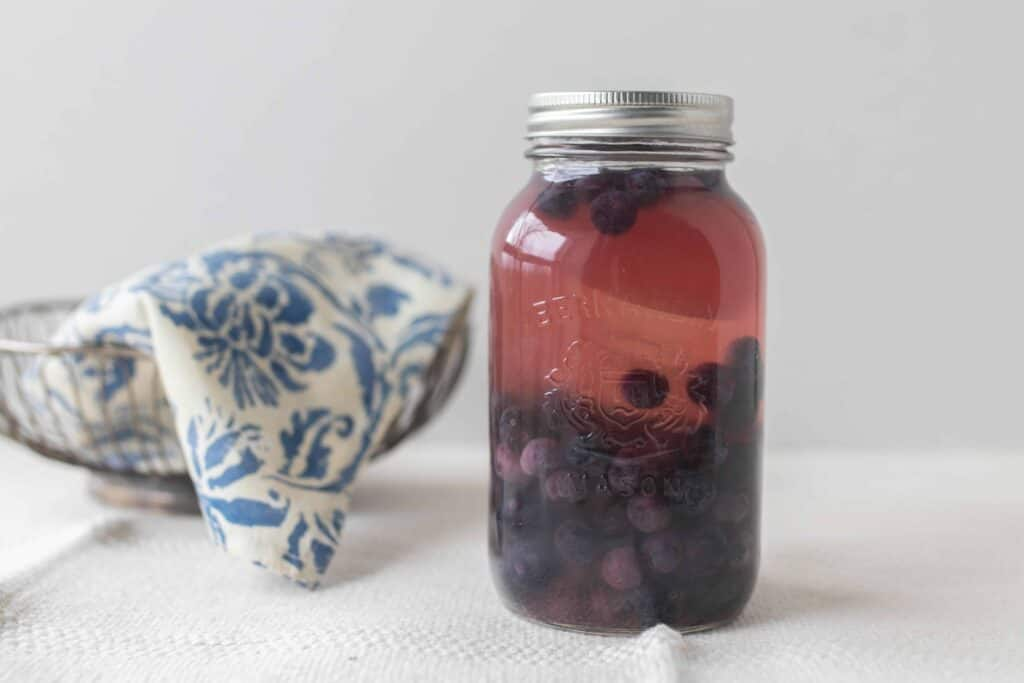 Fermented blueberries in a mason jar with a silver bowl covered with a blue and white damask printed towel in the background