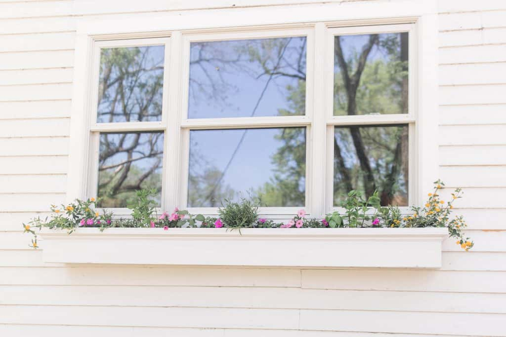 a white diy window box hanging below a window with yellow and pink flowers