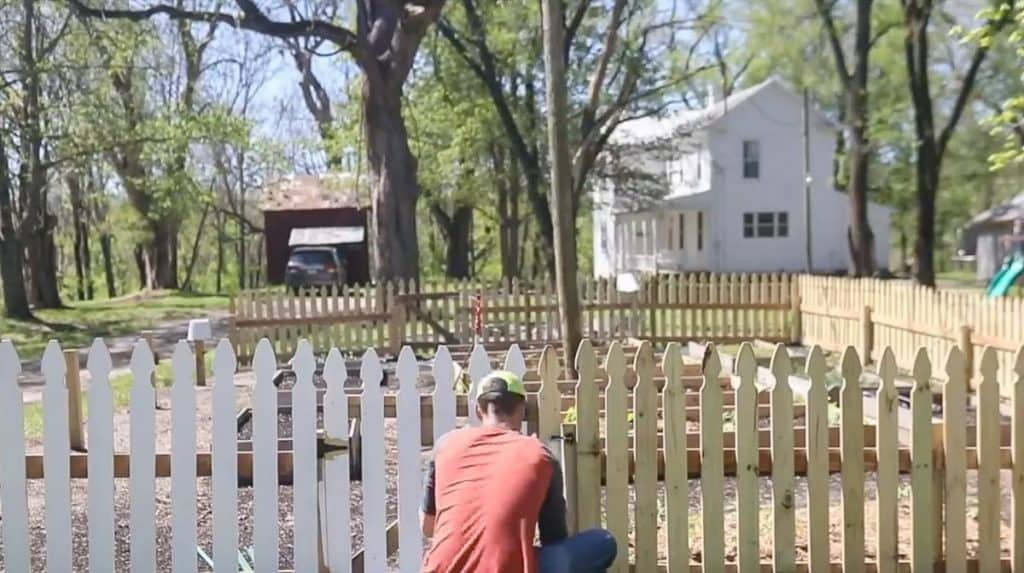 man wearing red shirt in painting a diy picket fence white with a roller