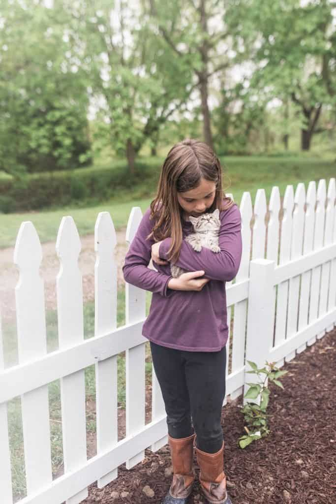 girl wearing a purple shirt cuddling a kitten in front of a DIY picket fence