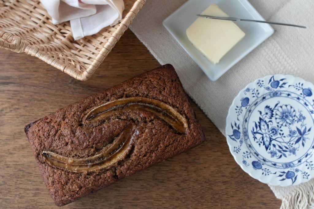 loaf of banana bread in a table with a blue and white place, white plate with butter, and a basket surrounding the loaf
