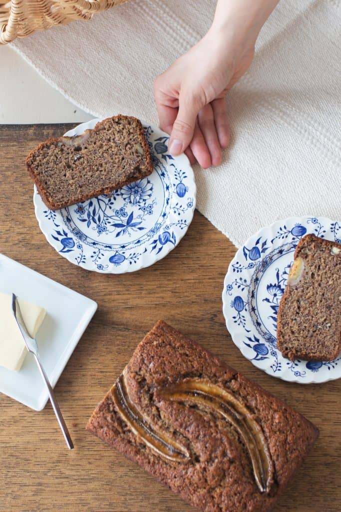 hand reaching to pick up a blue and white plate with a slice of sourdough banana bread on it. half a loaf of banana bread is in front of the plates on a table