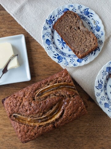 half loaf of sourdough banana bread on a table with two blue and white plates with slices of banana bread.