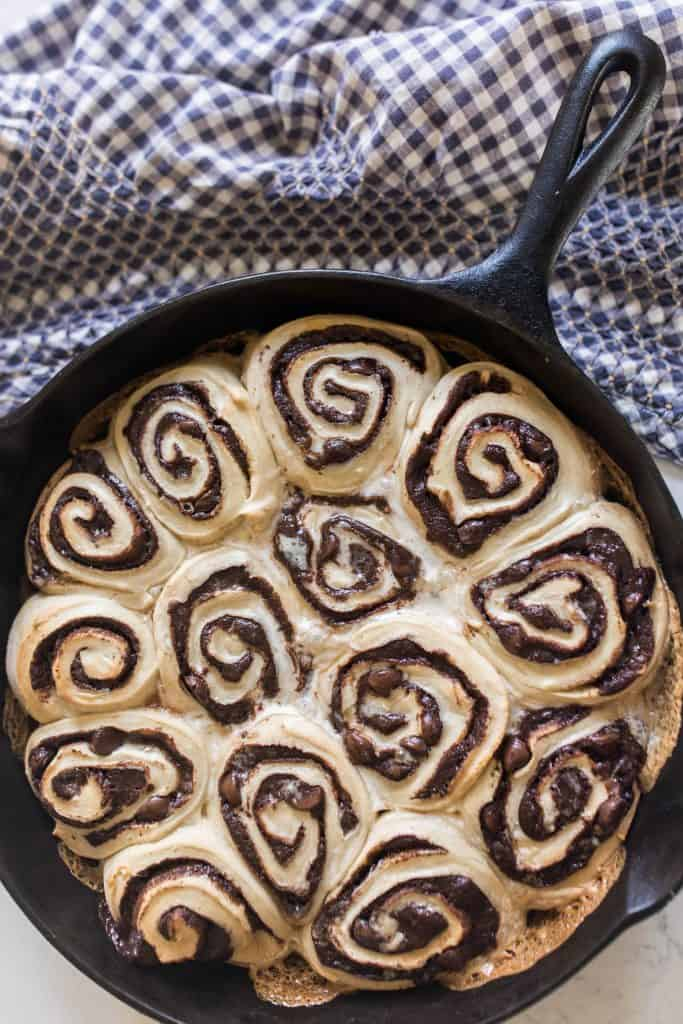 sourdough chocolate rolls in a cast iron skillet on a white and blue checked towel