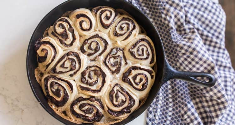 sourdough chocolate rolls in a cast iron skillet with a blue and white checked towel to the right