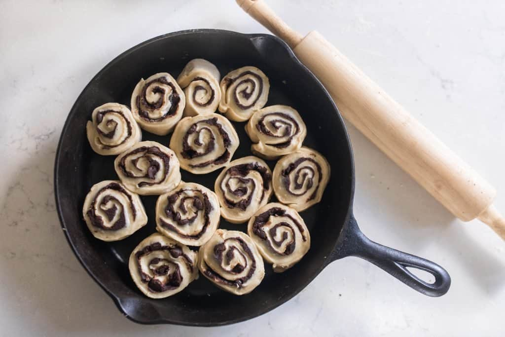 raw sourdough chocolate rolls in a cast iron skillet ready to be baked
