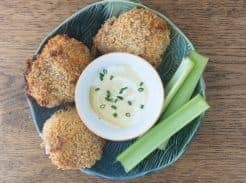 three sourdough fried chicken thighs in a tin bowl with a small bowl of mustard dipping sauce and celery sticks to the right