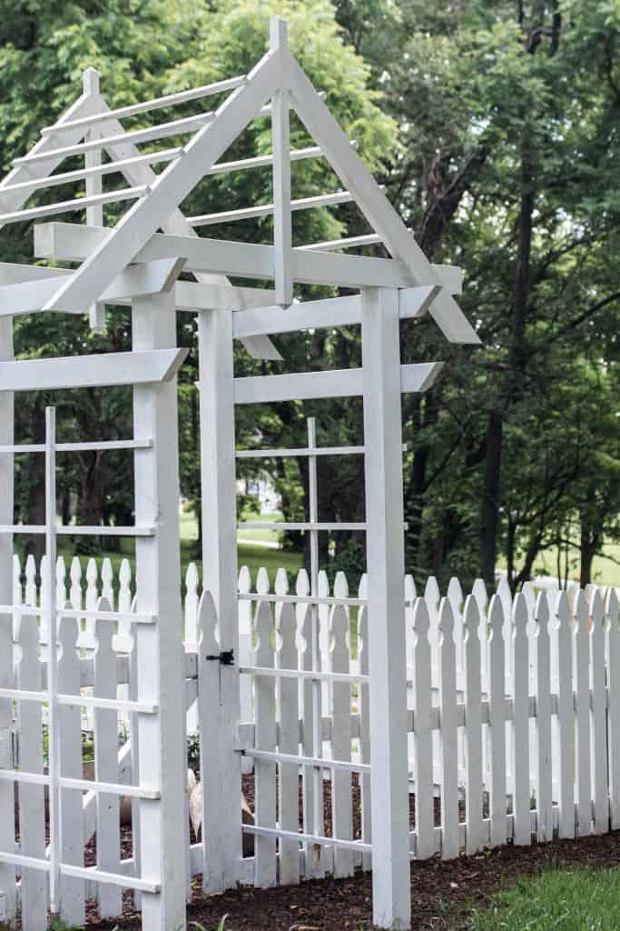 white arbor next to a white picket fence going into a garden